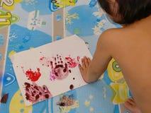 Mała Azjatycka dziewczynka robi handprint, odcisk palca obrazowi na/białej księgi w domu - dziecka handprint, odcisk palca obr zdjęcia stock