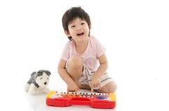 Mała azjatykcia chłopiec bawić się elektrycznego zabawkarskiego pianino fotografia stock