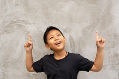 Mała azjatykcia chłopiec ono uśmiecha się z palca wskazywać oddolny zdjęcie royalty free