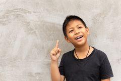 Mała azjatykcia chłopiec ono uśmiecha się z palca wskazywać oddolny zdjęcia stock