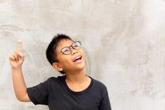 Mała azjatykcia chłopiec ono uśmiecha się z palca wskazywać oddolny fotografia royalty free