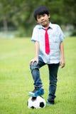Mała azjatykcia chłopiec z futbolem przy parkiem Obrazy Stock