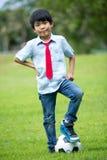 Mała azjatykcia chłopiec z futbolem przy parkiem Zdjęcie Stock
