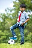 Mała azjatykcia chłopiec z futbolem przy parkiem Zdjęcia Royalty Free