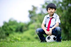 Mała azjatykcia chłopiec z futbolem przy parkiem Fotografia Stock