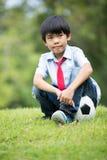 Mała azjatykcia chłopiec z futbolem przy parkiem Zdjęcia Stock