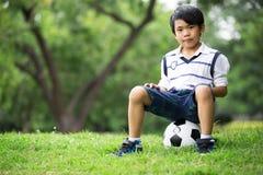 Mała azjatykcia chłopiec z futbolem przy parkiem Fotografia Royalty Free