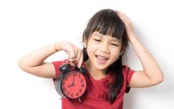 Mała azjatykcia dziewczyna jest gniewna przy budzikiem dla budzić się ona up Zdjęcie Royalty Free