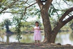 Mała azjatykcia dziewczyna z drzewną pobliską laguną Fotografia Royalty Free