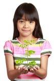 Mała azjatykcia dziewczyna z rozsadowym przyrostem od monet obraz royalty free