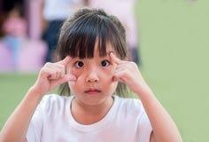 Mała azjatykcia dziewczyny próba pokazywać dużych oczy Obraz Stock