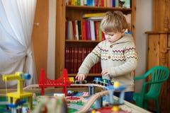 Mała berbeć chłopiec bawić się z drewnianą koleją, indoors Obrazy Stock