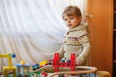 Mała berbeć chłopiec bawić się z drewnianą koleją, indoors Zdjęcie Royalty Free