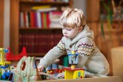 Mała berbeć chłopiec bawić się z drewnianą koleją, indoors Fotografia Royalty Free