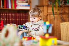 Mała berbeć chłopiec bawić się z drewnianą koleją, indoors Obraz Royalty Free