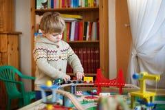 Mała berbeć chłopiec bawić się z drewnianą koleją, indoors Zdjęcie Stock