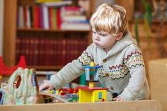 Mała berbeć chłopiec bawić się z drewnianą koleją, indoors Obrazy Royalty Free