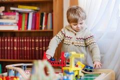 Mała berbeć chłopiec bawić się z drewnianą koleją, indoors Obraz Stock