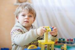 Mała berbeć chłopiec bawić się z drewnianą zabawką, indoors Obraz Royalty Free