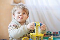 Mała berbeć chłopiec bawić się z drewnianą zabawką, indoors Zdjęcia Royalty Free
