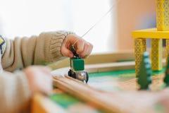 Mała berbeć chłopiec bawić się z drewnianą zabawką, indoors Zdjęcie Stock