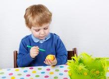 Mała berbeć chłopiec maluje tradycyjnego Wielkanocnego jajko dla polowania Fotografia Royalty Free