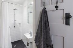 Mała biała kafelkowa ensuite łazienka z prysznic i wiszącym ręcznikiem fotografia royalty free