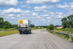 Mała biel ciężarówka z ogonu dźwignięciem i dużym uśmiechem iść na autostradzie między miastami obrazy stock