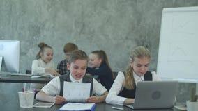 Mała blond dziewczyna i chłopiec w garnituru obsiadaniu przy stołem w biurowym działaniu na laptopie wtedy zamyka je pisze puszku zbiory