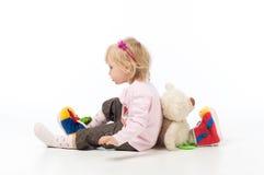 Mała blond dziewczyna siedzi z powrotem popierać z zabawka niedźwiedziem zdjęcie royalty free
