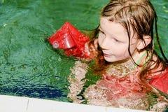 Mała blond dziewczyna z armband unosi się w pływackim basenie Dziecko uczy się swimm Zdjęcia Royalty Free