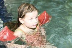 Mała blond dziewczyna z armband unosi się w pływackim basenie Dziecko uczy się swimm Obrazy Stock