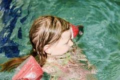 Mała blond dziewczyna z armband unosi się w pływackim basenie Dziecko uczy się swimm Fotografia Royalty Free