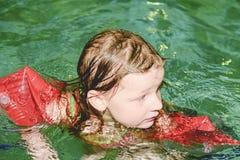 Mała blond dziewczyna z armband unosi się w pływackim basenie Dziecko uczy się swimm Zdjęcie Stock