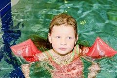 Mała blond dziewczyna z armband unosi się w pływackim basenie Dziecko uczy się swimm Fotografia Stock