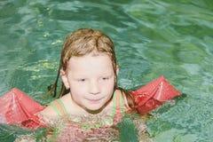 Mała blond dziewczyna z armband unosi się w pływackim basenie Dziecko uczy się swimm Obraz Royalty Free