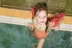 Mała blond dziewczyna z armband unosi się w pływackim basenie Dziecko uczy się swimm Dziewczyna odpoczynku basenu publicznie Obraz Stock