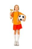 Mała blond dziewczyny mienia piłki nożnej piłka i nagroda zdjęcie royalty free