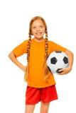 Mała blond dziewczyny mienia piłki nożnej piłka odizolowywająca obraz stock