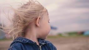 Mała blondynki dziewczyna patrzeje w odległość i trzyma piasek zbiory wideo