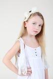Mała boleściwa dziewczyna w czystej biel sukni z łękiem w jej włosy obraz stock