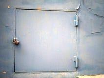 Mała brama z kłódką na jasnej błękit ścianie obraz stock