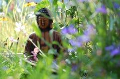 Mała Buddha statua w łące wildflowers Zdjęcie Royalty Free