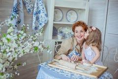 Mała córka całuje jej matki na kuchni Obrazy Stock