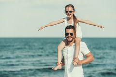 Mała córka w okularach przeciwsłonecznych siedzi na ojciec szyi zdjęcia royalty free