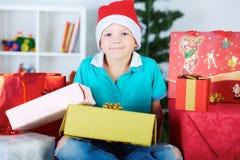 Mała caucasian chłopiec w Santa czerwonym kapeluszu z mnóstwo prezentów pudełkami Obraz Stock