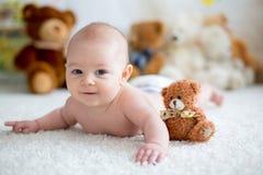 Mała chłopiec bawić się z miękkim misiem w domu bawi się Obraz Royalty Free