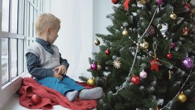 Mała chłopiec dekoruje choinki bawi się Wakacje, prezent i nowego roku pojęcie, zbiory wideo