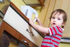 Mała chłopiec dosięga eletrical czajnika z gorącą wodą Zdjęcia Stock