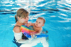 Mała chłopiec i jego macierzysty uczenie pływać w salowym swi Zdjęcia Royalty Free